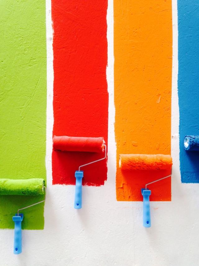 Different colored paint rollers on wall